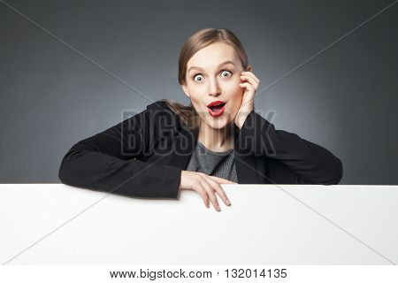 Surprised woman with open mouth looking at camera.Blank space