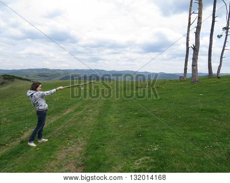 The girl raised her stick in the mountains and shows it to the side.