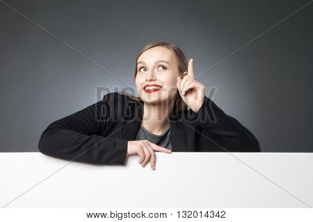 Beautiful businesswoman looking up with index finger up