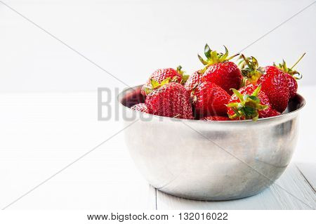 Fresh strawberries on white wooden background. Kitchen still life on table top.
