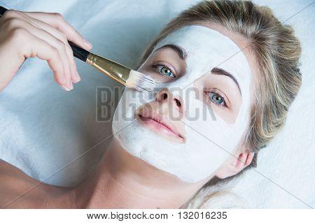 Beautiful woman with facial mask at beauty salon spa