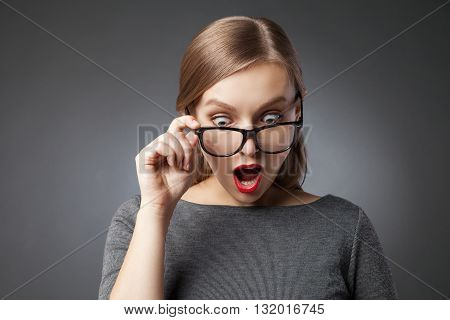 Amazed woman with red lips in glasses looking down with open mouth