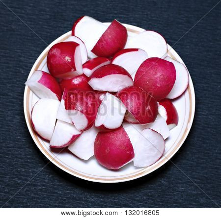 Sliced red fresh radishes on a plate on a dark background