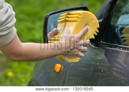 hand of woman washing car with sponge closeup