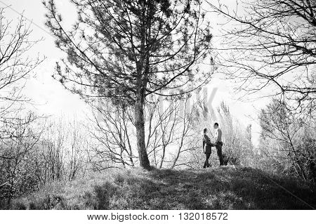 Pretty Couple Stay And Holding Hands On A Hill With A Tree. Black And White Photo