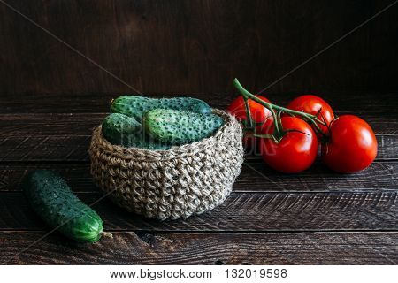 cucumbers and tomatoes fragrant green cucumbers green cucumber on brown background basket made of jute branch of red tomatoes.