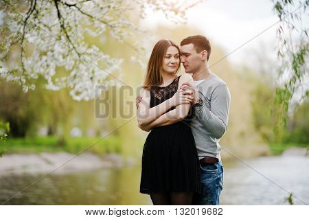 Young Couple In Love Outdoor Background Lake With Blossom Tree