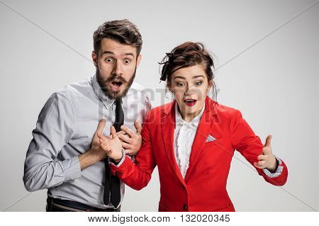 The funny surprised business man and woman smiling on a gray background. Business concept of relationship