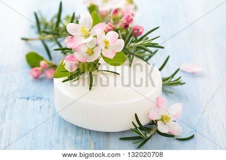 Bar of white soap with apple blossom and rosemary on old wooden table.