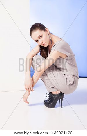 Beautiful brunette in earrings, suit and high heels sitting on haunches in studio.