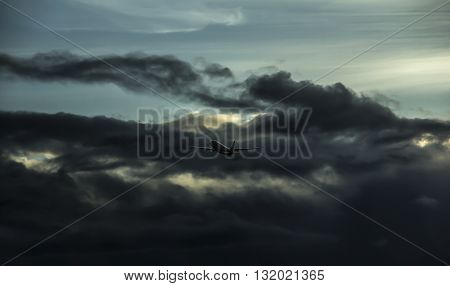 outline of an airplane flying into thunderstorm cloud