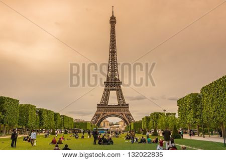 PARIS FRANCE - MAY 07 2015: Tourist sitting in the park near famous Tour Eiffel in Paris France
