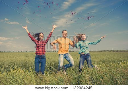 Young happy Friends running on green wheat field. One guy and two girls are jumping having fun.