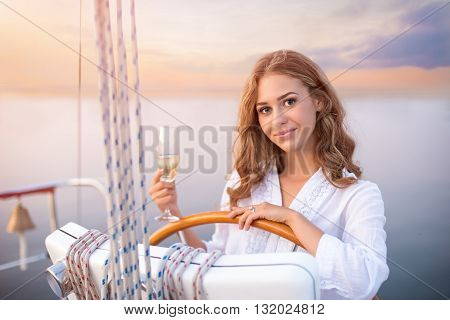 Smiling girl at yacht wheel. Young female holding a drink. Have a happy holiday. Enjoy every day of life.