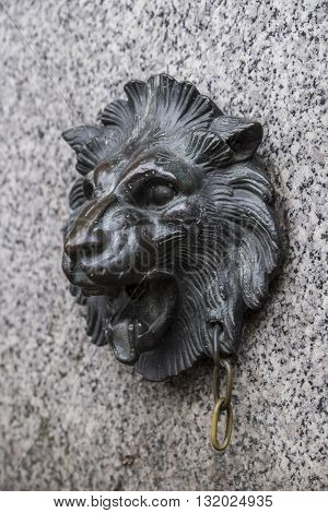 Ornate lion's head in brass on a stone wall