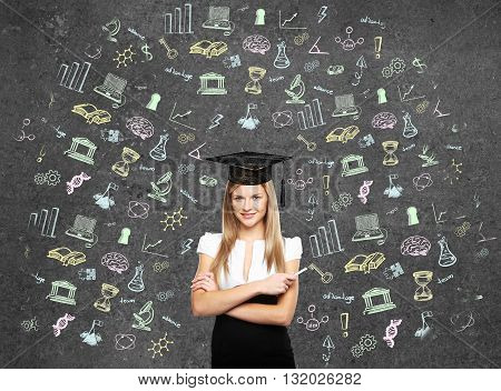 student woman in bachelor hat and drawing education simbol on wall