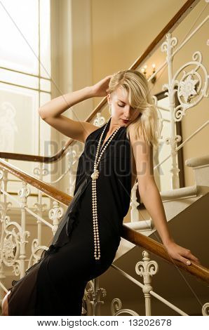 Beautiful young woman standing on a staircase