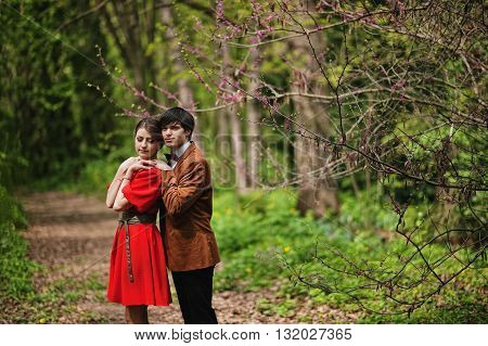 Couple Hugging At Forest With Spring Branches. Stylish Man At Velvet Jacket And Girl In Red Dress In