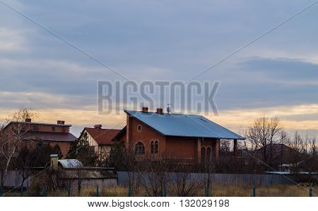 homes and evening sky with clouds of different colors