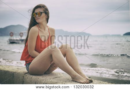 Young Woman Sitting On The Beach During Vacation