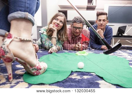 group of young adults have fun playing golf in the living room