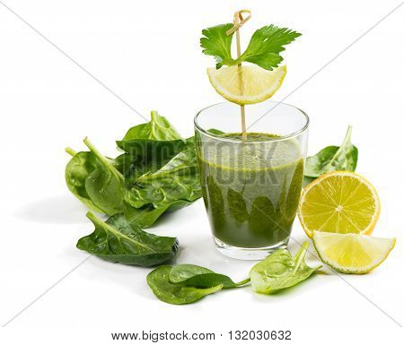 Green smoothie of spinach in a glass decorated with lemon isolated on white background.