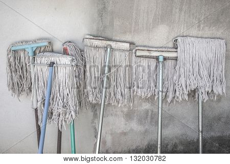 Six white mops lean against white wall revealed to sunlight exposure, white wall background
