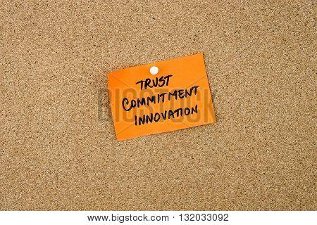Trust, Commitment, Innovation Written On Orange Paper Note