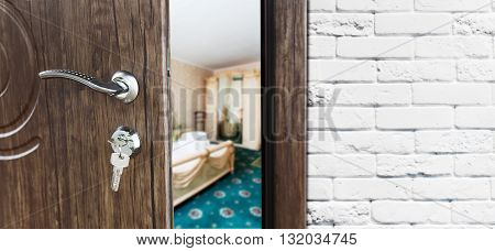 Half opened door to a bedroom. Door handle, door lock. Lounge door half open. Opening door. Welcome, privacy concept. Entrance to the room. Door at white brick wall, modern interior design.