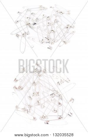 Surface covered with multiple metal safety pins isolated on white background, set of different foreshortenings