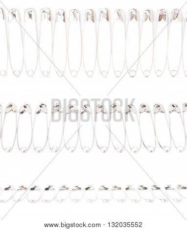 Line border made of multiple metal safety pins isolated on white background, set of different foreshortenings