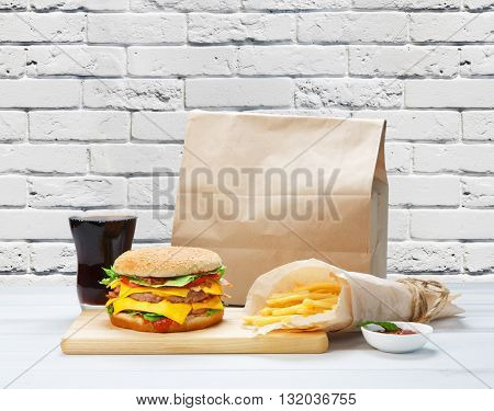 Fast food. Brown wrapping paper package with copyspace. Hamburger, potato fries, drink at brick wall background. Takeaway food. French fries, packaging, Cola glass, big cheese hamburger at wood.