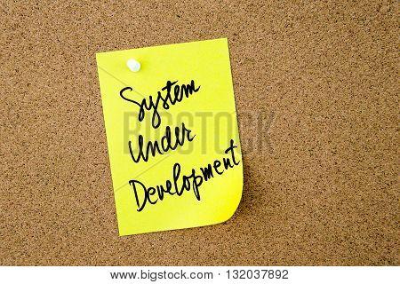 System Under Development Written On Yellow Paper Note
