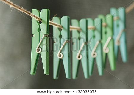 Row of pins green hanging from a rope focusing differed in one of them and leaving the rest blurred
