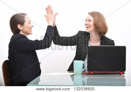 Business women and high five while celebrating a business accomplishment