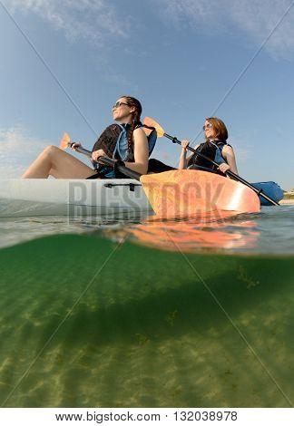 women smiling in blue kayak in ocean off of the coast of Florida