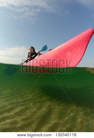 young woman in ocean in pink kayak