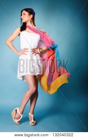 Summer fashion. Full length beauty young woman fashionable sensual girl with multicolored flying shawl on blue background