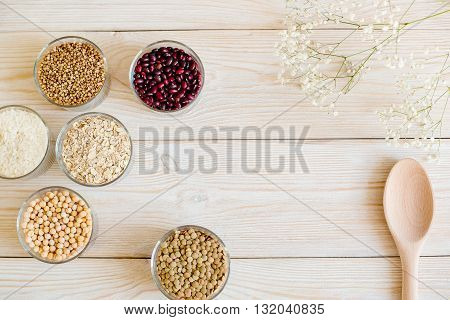 Grain and beans in glass bowls on a white wooden background. with lovely flowers and rustic spoon Various types of grain. beans, peas, buckwheat, lentils, rice. healthy food and diet concept. top view