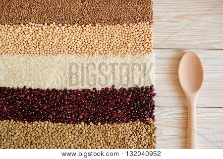 Grain and beans with rustuc spoon on a white wooden background. Various types of grain. beans, peas, buckwheat, lentils, rice. healthy food and diet concept. Grain abd beans background. top view