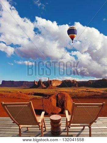 Red sandstone in the valley of the Navajo, USA. Two wooden deck chairs on the platform are to observe the Monument Valley