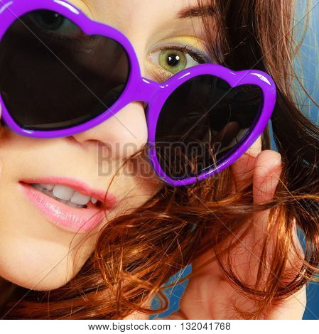 Summer fashion eyes protection concept. Closeup girl long curly hair in violet heart shaped sunglasses on blue