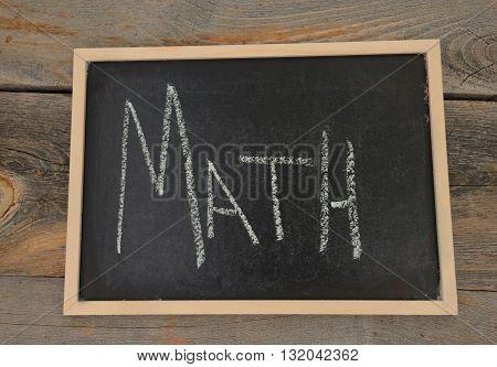 Math written in chalk on a chalkboard on a rustic background