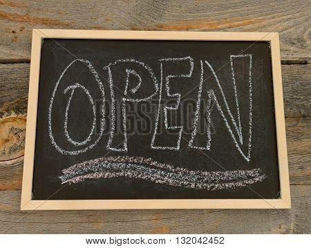 open written in chalk on a chalkboard on a rustic background