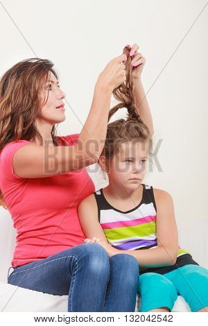 Mother combing daughter care about hairstyle. Girl is unhappy mom pulling her hair. Important role in child life.