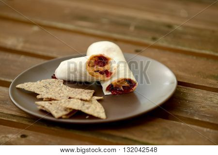 peanut butter and jelly wrap with chips on a plate