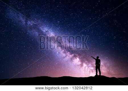 Milky Way with silhouette of a standing young man pointing finger in night starry sky on the mountain. Night landscape. Beautiful Universe travel background with purple sky full of stars and yellow light