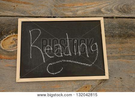 Reading written in chalk on a chalkboard on a rustic background