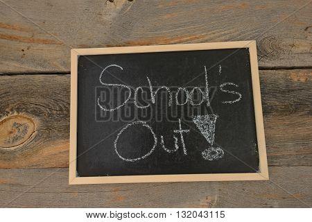 school's out written in chalk on a chalkboard on a rustic background