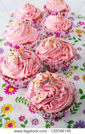 Pink cupcakes on floral pattern napkin. Homemade cupcake. Sweet dessert. Sweet pastry. Gourmet cupcakes. Sweet cupcake. Birthday cupcakes.